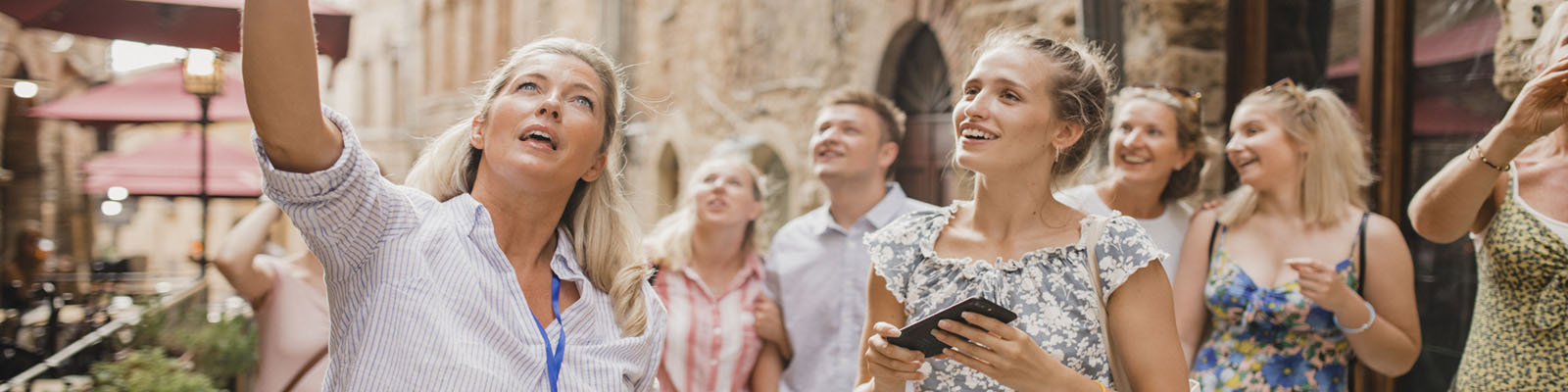 Medium group of people standing in a street in Volterra. They're listening to a tour guide who is talking about the architecture and the history.